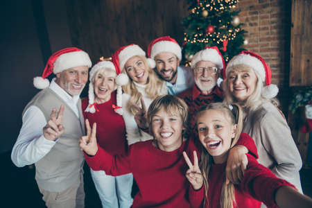 Self-portrait of nice positive cheerful big full family brother sister wearing cap hat headwear generation gathering tradition meeting eve noel showing v-sign in loft industrial style interior house