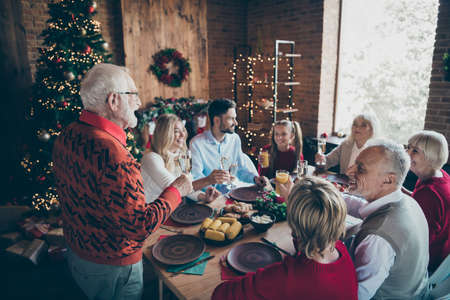 Nice lovely friendly cheerful big full family enjoying domestic tradition gathering eating homemade brunch granddad saying toast congrats in modern industrial loft brick style interior decorated house