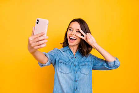 Portrait of cheerful positive girl photographer take selfie with cell phone on journey vacation make v-signs have fun feel funny funky wear denim jeans shirt isolated over yellow color background