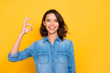 Portrait of cheerful positive promoter have fun show ok sign recommend information about discounts sales wear trend clothes isolated over yellow color background Stock fotó