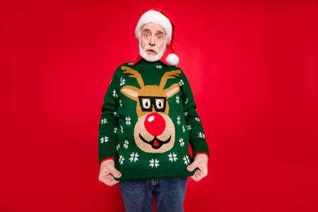 Foto von Santa Opa, der einen hässlichen Hirschverzierungspullover zeigt, der auf sich selbst gekleidet ist, versteht die Idee des Kostümthemas Weihnachtsfeiern isoliert auf rotem Hintergrund nicht