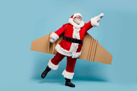 Full length body size view of his he nice fat focused purposeful St Nicholas Santa wearing warm coat plane wings flying fast hurry up delivering gifts isolated over blue pastel color background