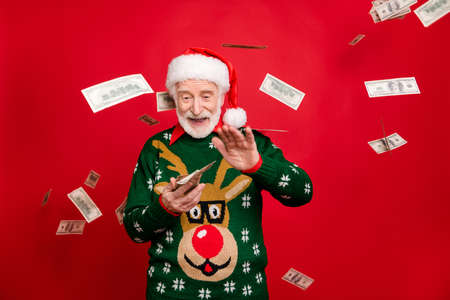 Portrait of funny funky crazy grey white hair beard old man wear santa claus hat antler design sweater throw cashback income he won in x-mas lottery isolated red color background with money fall fly Фото со стока