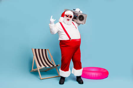 Full length body size view of his he nice naughty glad cheerful cheery fat Santa dj carrying retro tape player showing horn sign isolated over blue turquoise pastel color background