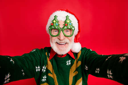 Closeup photo of funny aged santa claus role man making crazy selfies wear x-mas tree shape specs knitted sweater hat isolated red background