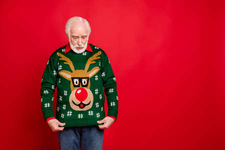 What did i get. Portrait of amazed shocked old man look at reindeer pattern sweater for christmas theme party received as newyear party isolated over red color background