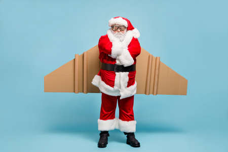 Full length body size view of his he nice fat dissatisfied moody sullen St Nicholas Santa wearing warm coat plane wings folded arms isolated over blue pastel color background