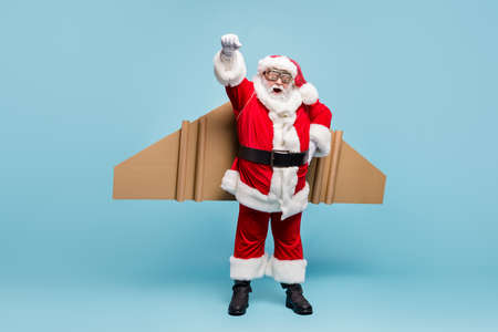 Full length body size view of his he nice fat cool glad cheerful cheery excited bearded Santa wearing plane wings fast shipping shop delivery service isolated over blue pastel color background