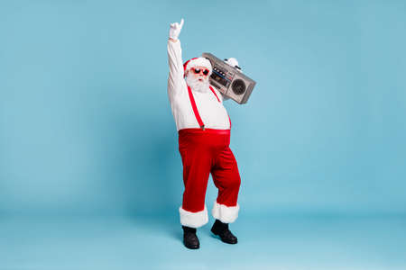 Full length body size view of his he nice cool stylish cheerful Santa big belly pants carrying vintage cassette player dancing isolated on bright vivid shine vibrant blue turquoise color background Standard-Bild - 131544062