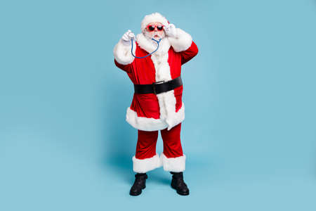 Full length body size view of his he nice funky bearded Santa Claus wearing phonendoscope making diagnostic isolated over blue turquoise pastel color background Stock Photo