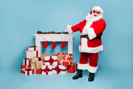 Full length body size view of his he nice fat cheerful cheery glad bearded Santa standing near fire place showing demonstrating pile stack purchases isolated on blue turquoise pastel color background Banco de Imagens