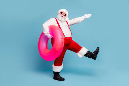 Full length body size view of his he nice cool cheerful cheery fat Santa walking carrying pink life buoy pool party isolated over blue turquoise pastel color background Stock fotó