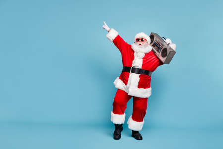 Full length body size view of his he nice cool trendy stylish fat cheerful cheery glad excited bearded Santa carrying tape player dancing isolated over blue turquoise pastel color background Standard-Bild - 131544083