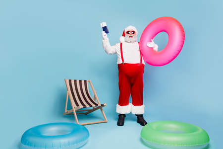 Full length body size view of his he nice glad cheerful fat bearded Santa traveler holding in hands pink circle docs having fun time isolated over blue turquoise pastel color background