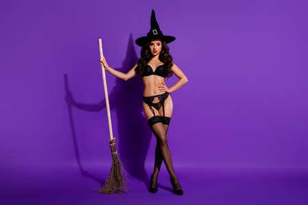 Vue sur toute la longueur du corps d'elle, elle est belle et séduisante femme aux cheveux ondulés séduisante posant avec un balai isolé sur un fond de couleur violet violet violet lilas vif éclatant