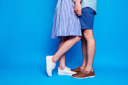 Cropped view of his he her she two nice attractive people legs holding hands going out on date isolated over bright vivid shine vibrant blue turquoise color background