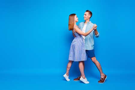 Ganzkörperansicht von ihr, sie sind seine zwei hübsch aussehenden, attraktiven, charmanten, fröhlichen Menschen, die Walzer tanzen, einzeln auf hell leuchtendem, leuchtend blauem, türkisfarbenem Hintergrund