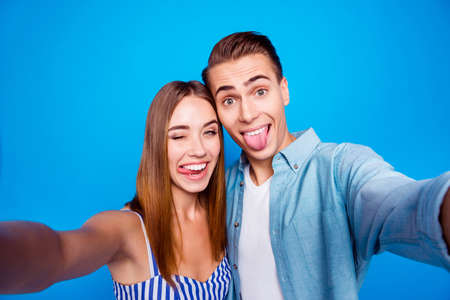 Self-portrait of her she his he two nice attractive lovely crazy hilarious playful cheerful cheery glad people showing tongue out isolated over bright vivid shine vibrant blue color background Banco de Imagens