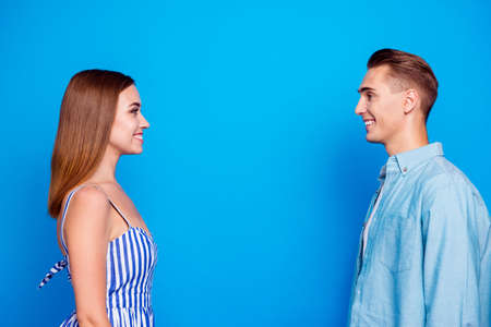 Profile side view portrait of her she his he two nice attractive charming lovely content cheerful cheery people looking at each other isolated over bright vivid shine vibrant blue color background 写真素材