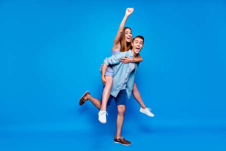 Full length body size view of two nice attractive overjoyed cheerful cheery glad positive people piggy-backing having fun fooling isolated on bright vivid shine vibrant blue color background