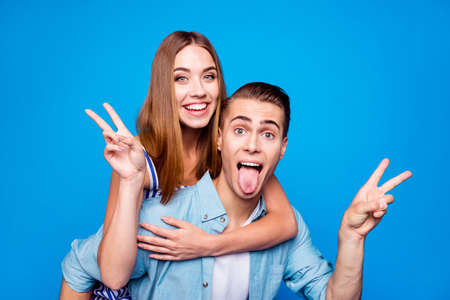Close-up portrait of two nice attractive crazy foolish cheerful cheery glad positive people piggy-backing showing v-sign having fun fooling isolated on bright vivid shine vibrant blue color background