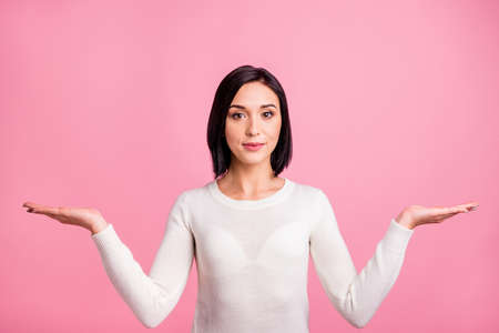 Photo of pretty sale manager lady presenting novelty on both arms offer to pick better product wear white pullover isolated pink color background