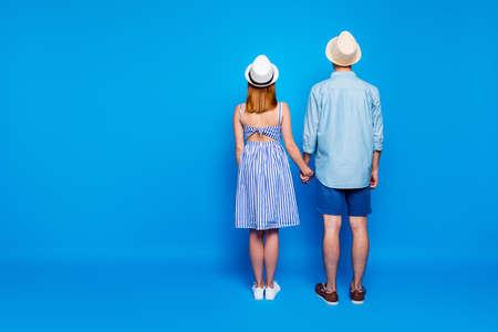 Parte trasera detrás de la vista del tamaño del cuerpo de cuerpo entero de él, ella, ella, dos personas atractivas y agradables cogidos de la mano, pasar el día de verano de vacaciones aislado sobre fondo de color azul vibrante de brillo vivo brillante