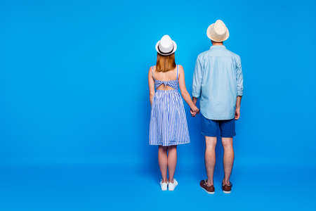 Rear back behind full length body size view of his he her she two nice attractive people holding hands spending vacation summertime day isolated on bright vivid shine vibrant blue color background
