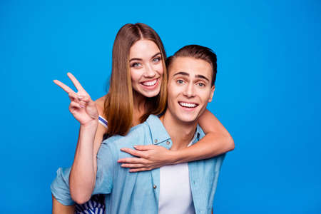 Close-up portrait of two nice attractive lovely funky cheerful cheery glad positive people piggy-backing showing v-sign isolated on bright vivid shine vibrant blue color background