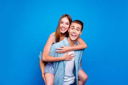 Portrait of his he her she two nice attractive lovely funky childish cheerful cheery glad excited positive people piggy-backing having fun isolated on bright vivid shine vibrant blue color background