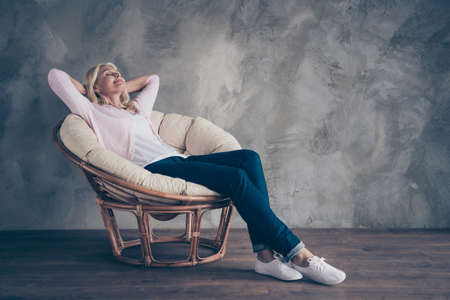 Full length photo of peaceful calm middle-aged woman lying in white wicker armchair dream have vacation wear pastel color sweater denim jeans in room