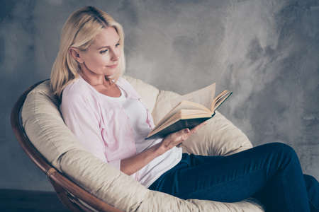 Portrait of focused middle aged woman in pastel color pullover denim jeans read book encyclopedia want know more have autumn vacation sit wicker chair indoors