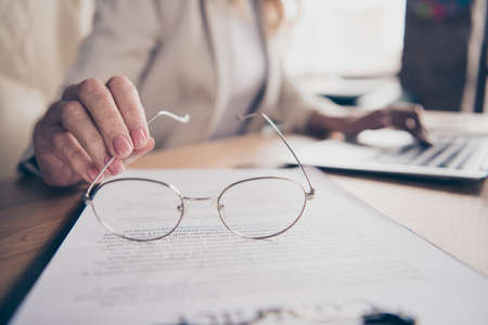 Cropped photo of eyewear, glasses held by entrepreneur while looking through contract paper attentively