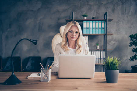 Photo of old white haired woman working with her laptop online with her coworkers using modern technology to communicate with corporation team