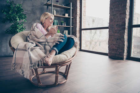 Full length profile side photo of charming peaceful dreamy middle aged woman sit in armchair covered with checkered blanket hold mug look window dream imagine autumn holidays indoors