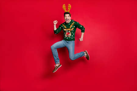 Full length photo of funky guy jumping high running fast to x-mas discounts shopping wear pullover with ugly deer ornament isolated red color background