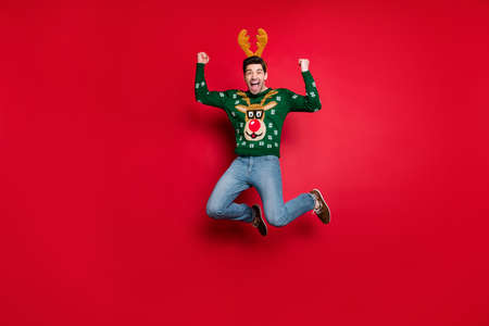 Full body photo of funky guy jumping high excited with x-mas discounts wear knitted green pullover with ugly deer ornament isolated red color background Stok Fotoğraf