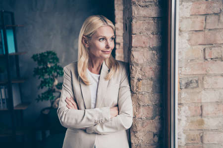Portrait of dreamy thoughtful middle aged businesswoman cross her hands look in window think about her start-up future seminars for workers wear stylish jacket stand brick wall in office company