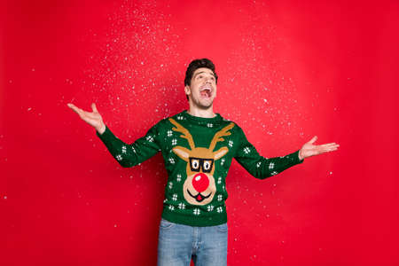 Portrait of his he nice attractive handsome cheerful cheery dreamy guy wearing green deer sweater enjoying leisure throwing snow isolated over bright vivid shine vibrant red color background