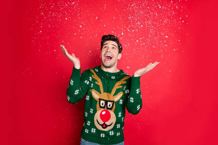 Portrait of his he nice attractive handsome cheerful cheery glad dreamy guy wearing green deer sweater throwing snow fairy miracle isolated over bright vivid shine vibrant red color background
