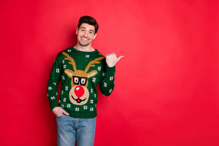 Portrait of funny festive brown hair in deer style stylish sweater point his thumb at copy space recommend winter shopping season sales isolated over red color background