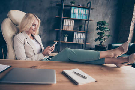 Portrait of charming middle aged blonde hair woman use cellphone have chat with her workforce career partners type messages sit in chair put her high-heels on wooden table 版權商用圖片