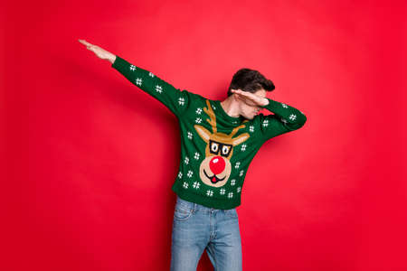 Portrait of his he nice attractive handsome cool guy wearing green deer sweater having fun dancing showing dab move isolated over bright vivid shine vibrant red color background