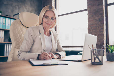 Photo of business lady making notes in her notebook when listening to words of speaker holding pen with hands