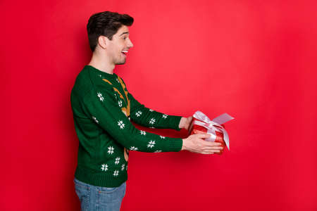 Profile side view portrait of his he nice attractive cheerful cheery glad guy wearing deer sweater giving festal gift isolated over bright vivid shine vibrant red color background Stock Photo