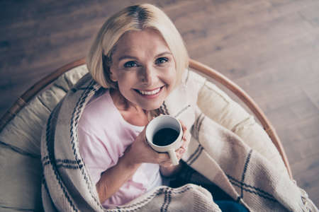 Top above high angle view photo of content positive middle aged woman hold cup mug with hot beverage cacao enjoy holidays sit soft wicker armchair in living room covered with checkered blanket Reklamní fotografie