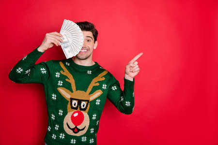 Photo of funny handsome guy holding fan of bucks in hands directing finger on x-mas sale banner wear knitted pullover with deer isolated red color background