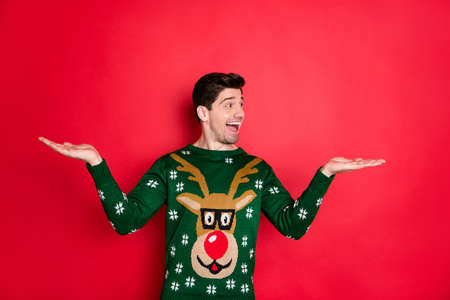Profile side photo of excited brunette hair man hold hand recommend winter season sales scream wow omg wear deer reindeer trendy fashionable jumper isolated over red color background