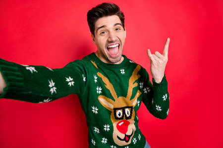 Portrait of funky funny crazy man in deer reindeer sweater make selfie show horned sign scream true rock-and roll heavy metal hipster on christmas event isolated over red color background