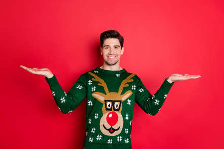 Portrait of cheerful funny man hold hand measuring adverts discounts wear stylish fashionable deer reindeer pullover isolated over red color background